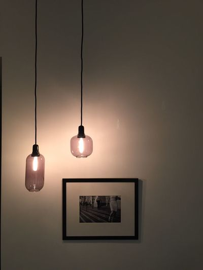 Low angle view of lit lamp hanging on ceiling