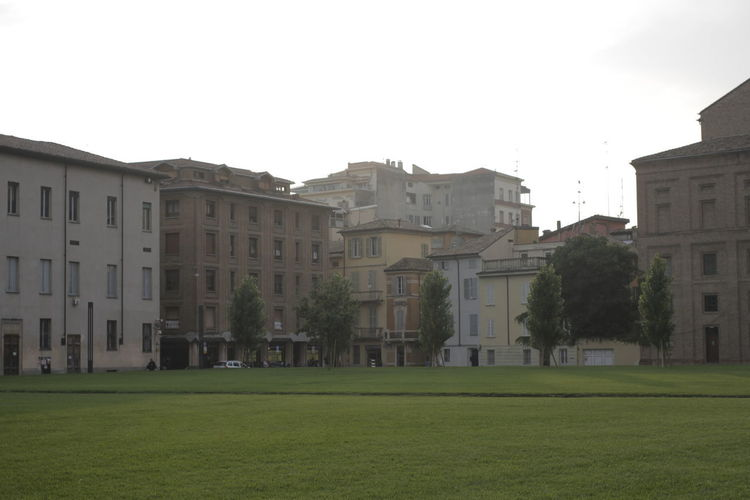 Buildings against clear sky with lawn in foreground