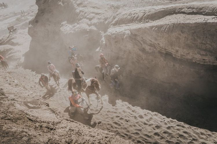 A group of people riding a horse to travel up the volcano  in the midst of the dust.