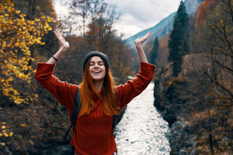 Smiling young woman with arms raised standing in autumn