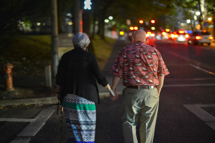 Rear View Of Couple Holding Hands While Walking On Road At Night