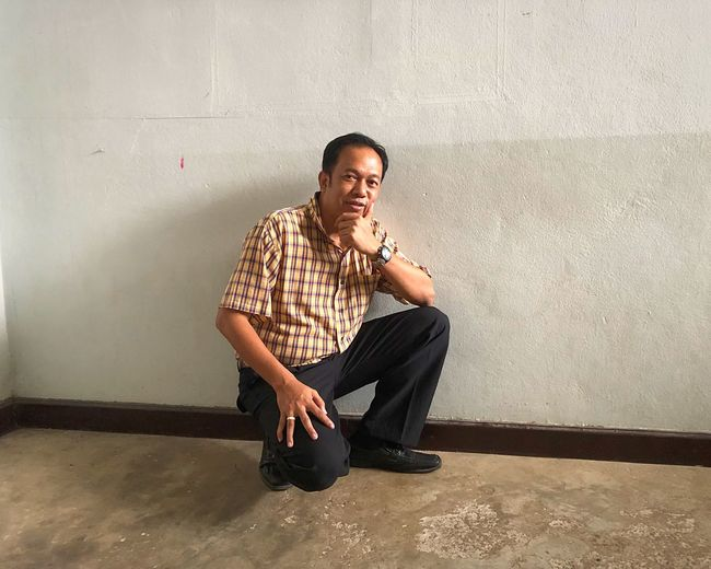 Portrait of mature man crouching against wall