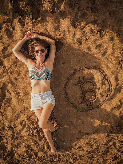 Full length of woman lying by bitcoin symbol at beach