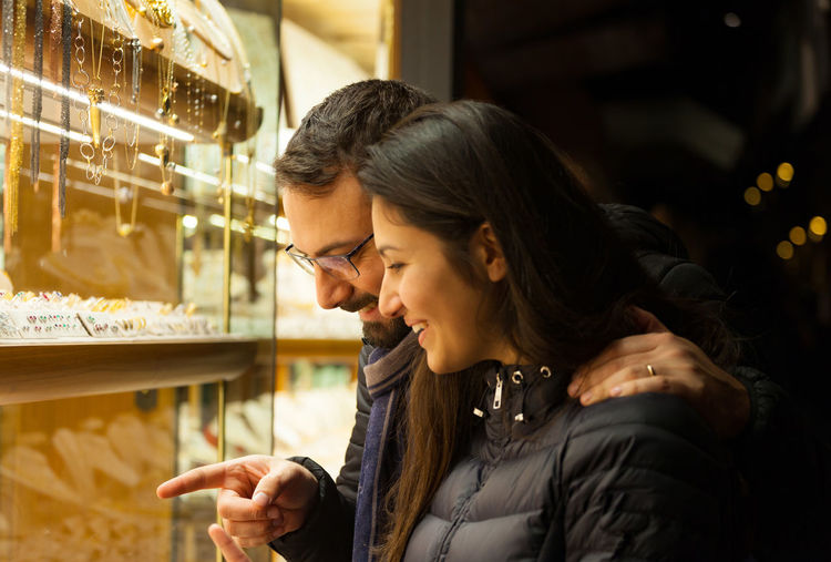 Smiling couple standing at jewelry shop at night