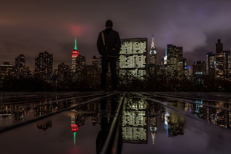 Rear view of man standing on glass floor against illuminated buildings