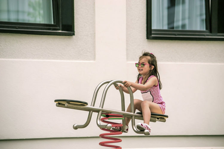 Full length of girl playing on seesaw by house