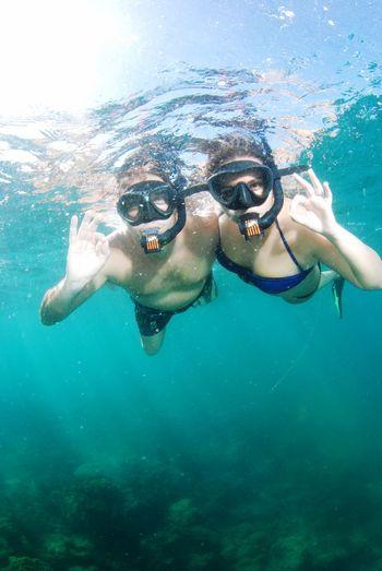 Portrait of couple swimming in sea