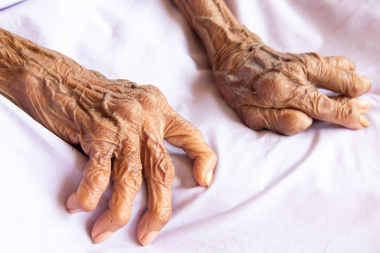 Cropped image of woman hand on bed