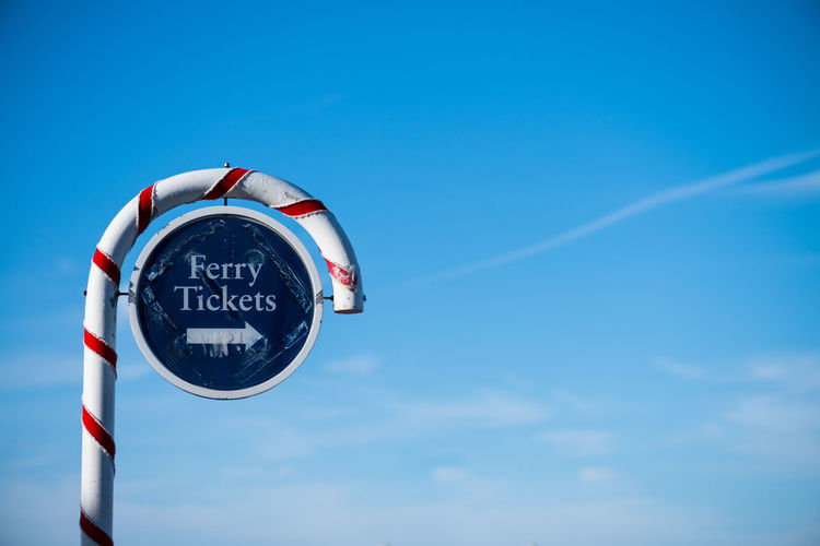 Ferry Tickets! Blue Circle Clear Sky Communication Copy Space Direction Ferry Ferry Tickets Guidance Information Sign Low Angle View Road Sign Sign Sky Text Tickets Transportation Western Script