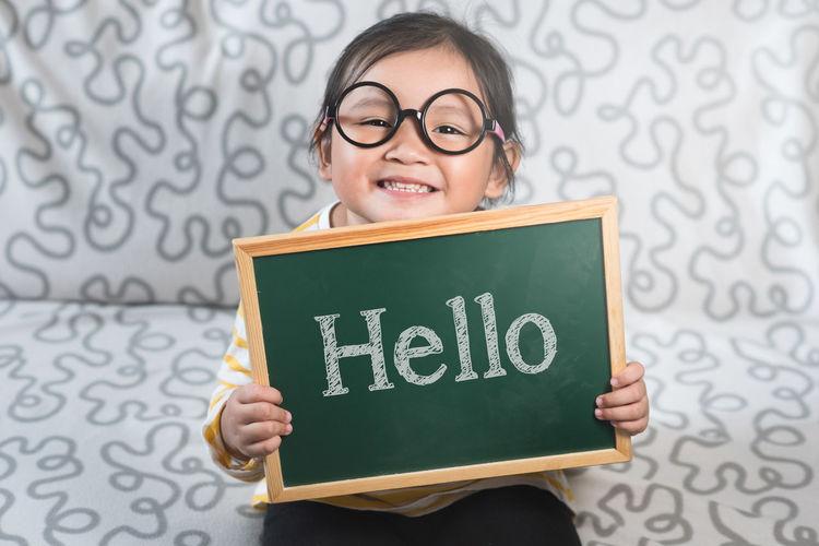 Portrait of a smiling girl holding eyeglasses