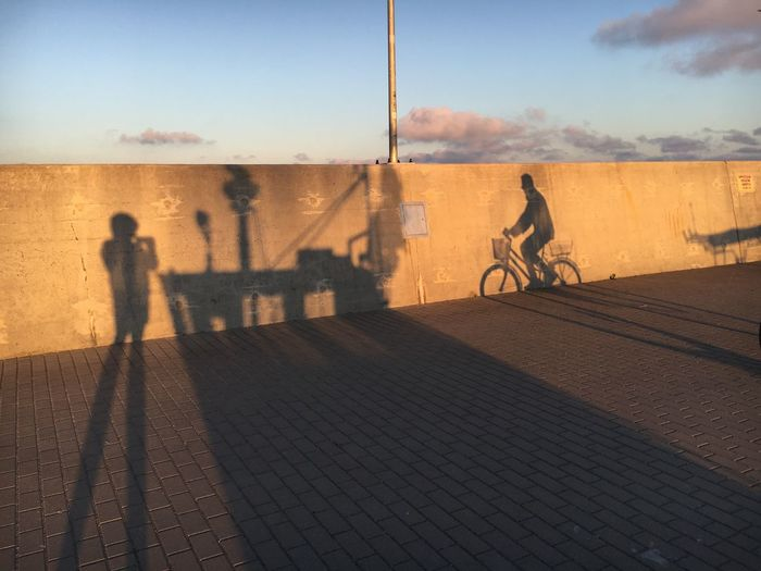 Shadow of man riding bicycle on street