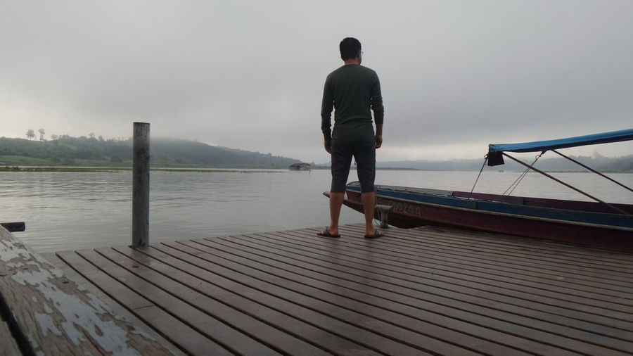 Rear view of man standing on pier by lake against sky