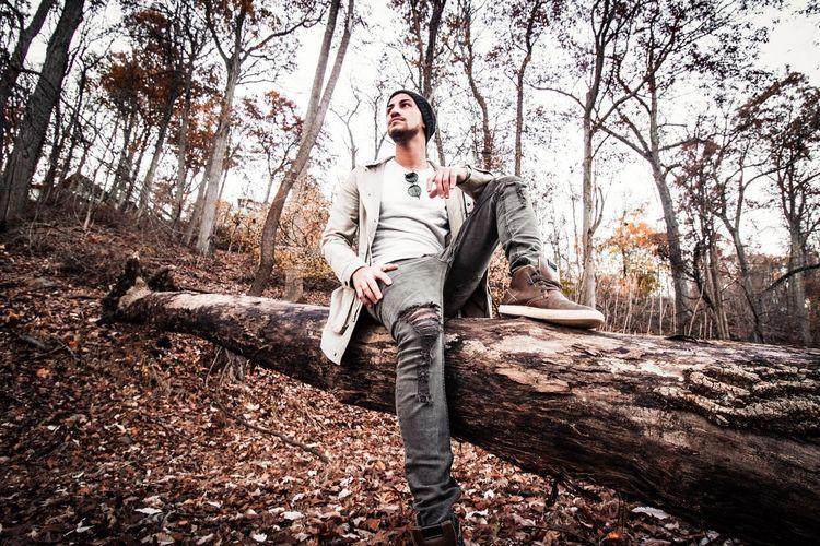Man sitting on fallen tree in forest