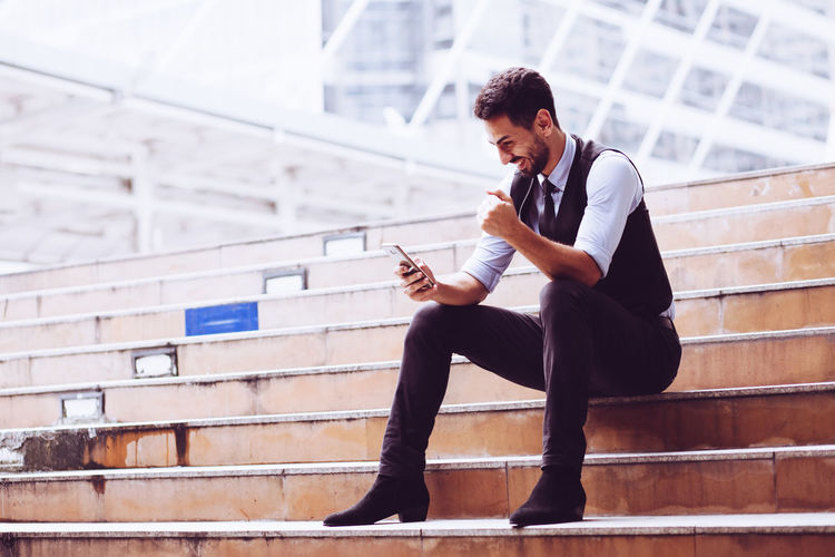 Young man using mobile phone while sitting on staircase