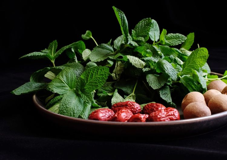 Food And Drink Food Freshness Healthy Eating Fruit Wellbeing Indoors  Black Background Green Color Leaf No People Plant Part Close-up Still Life Studio Shot Herb Bowl Plant Nature Mint Leaf - Culinary