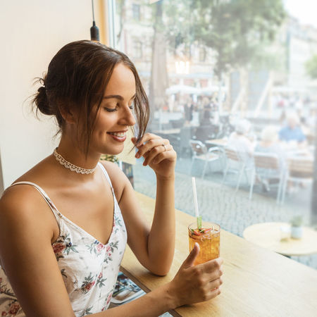 young woman having ice tea Dress Happiness Reflection Beautiful Woman Brunette Girl  Cafe Caucasian Drink Enjoying Life Food Food And Drink Holding Ice Tea Indoors  Lifestyles One Person Outdoors Sitting Smiling Straw Table Window Women Young Adult Young Adults