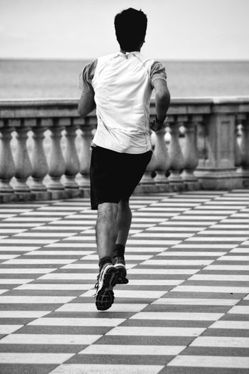 Rear View Of Man Jogging On Footpath By Sea