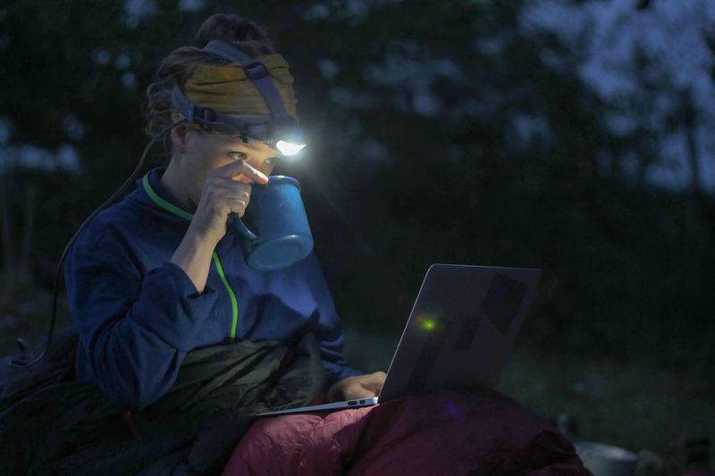 caucasian female hiker working on her laptop at night during wild camping, portable technology concept Backpacking Camping Dark Females Freedom Headlamp Hiking Nature Reading Travel Trekking Working Activity Adventure Battery Communication Computer Computer Network Connection Dark Evening Hobby Holding Internet Journal Land Laptop Leisure Activity Looking Nature Night One Person Outdoors People Portability Portable Information Device Sitting Technology Three Quarter Length Using Laptop Watching Wireless Technology Women