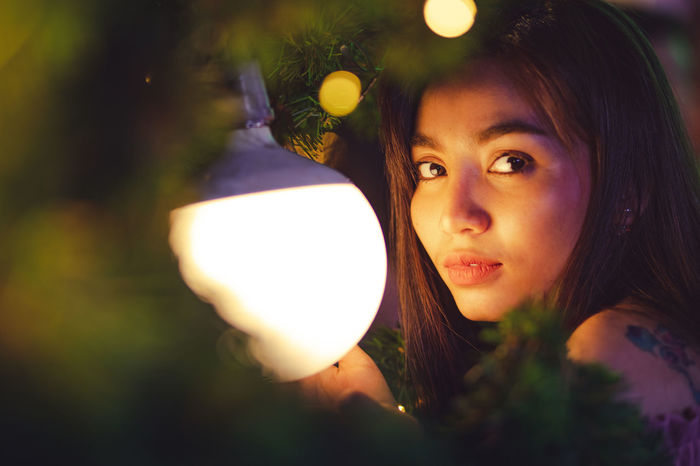 Portrait Headshot Real People One Person Looking At Camera Lifestyles Illuminated Young Adult Leisure Activity Women Young Women Focus On Foreground Close-up Hairstyle Glowing Holding Long Hair Beauty Beautiful Woman Outdoors Lens Flare Light Christmas Christmas Portrait Lighting
