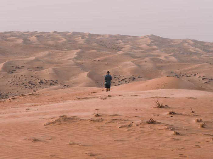 Man standing on sand dune in desert against sky