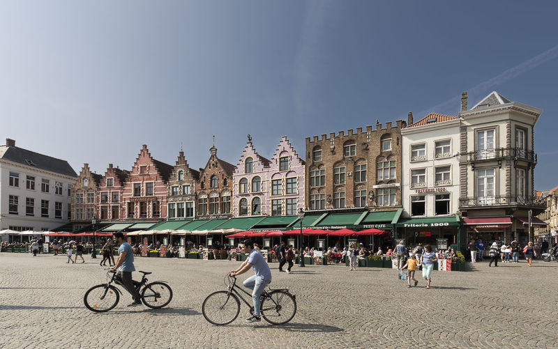 Bruges, Belgium May 9, 2018: Views of the market square in the city of Bruges with people going by bike in the foreground. Belgium Adult Architecture Bicycle Bruges Building Building Exterior Built Structure City Crowd Day Group Of People Land Vehicle Large Group Of People Men Mode Of Transportation Nature Outdoors Real People Riding Sky Street Transportation Turism Women