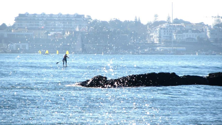 Man Paddleboarding On Sea In City