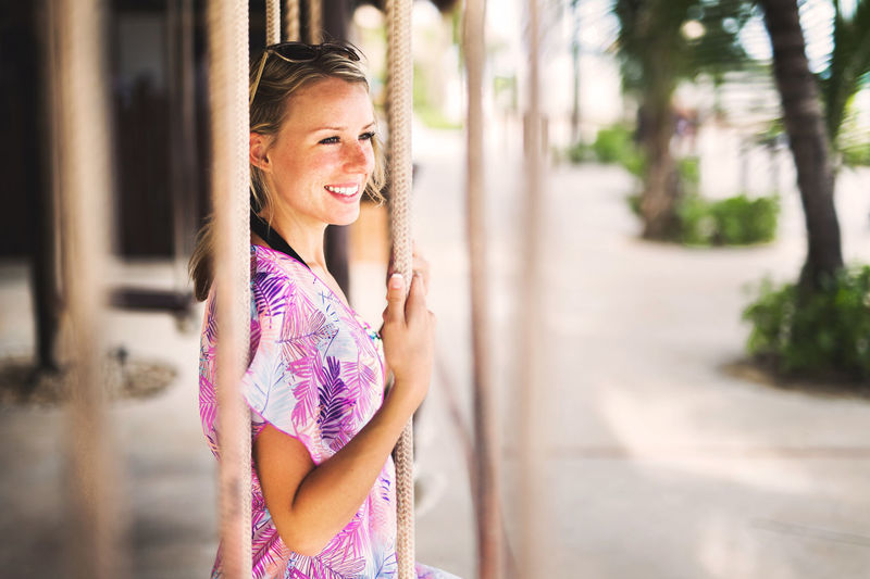 Looking Away Adult Architecture Bar Beautiful Woman Beauty Blond Hair Casual Clothing Day Happiness Lifestyles One Person Outdoors People Portrait Real People Smiling Standing Swing Young Adult Young Women