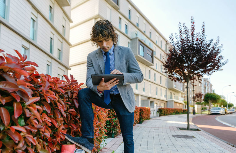 Young businessman with blazer and jeans working with the tablet in the street Business Horizontal Man Sunlight Tablet Worker Working Business Finance And Industry Businessman Caucasian Document Dossier Executive  Flare Holding Lifestyles Office Building One Person Outdoors Portfolio Professional Real People Street Sun Young Adult