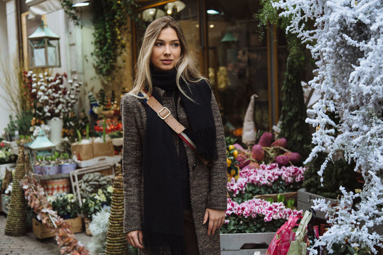 Thoughtful woman standing against flower shop in city