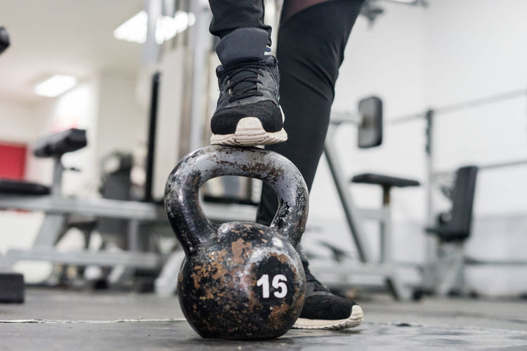 Low Section Of Person With Kettlebell Standing In Gym