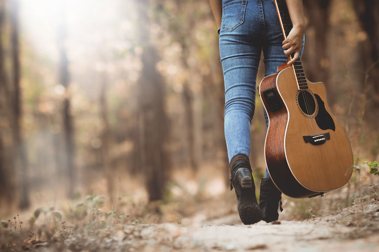 Musical Instrument Music String Instrument Land Guitar Tree Day Real People Forest One Person Nature Musical Equipment Leisure Activity Sunlight Musician Plant Focus On Foreground Arts Culture And Entertainment Musical Instrument String String Outdoors Acoustic Guitar Rock Music Portrait Conutryside