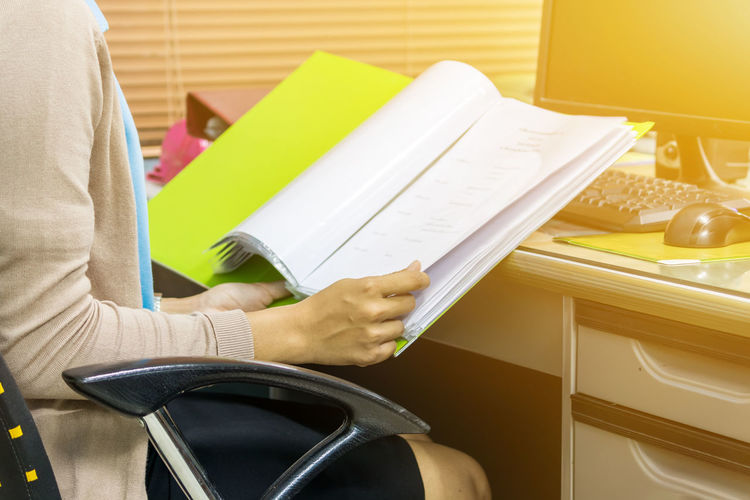 Midsection of businesswoman reading file while sitting at desk in office