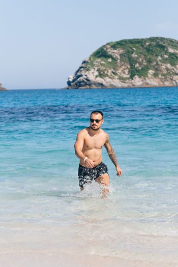Sea Shirtless Water Young Men One Person Lifestyles Leisure Activity Sky Young Adult Beauty In Nature Land Real People Beach Scenics - Nature Front View Day Men Nature Horizon Over Water Outdoors