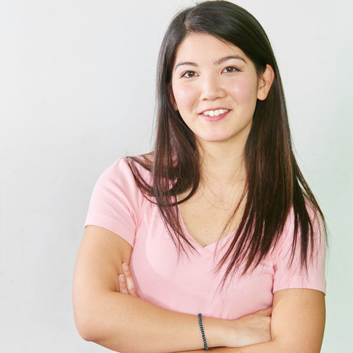 Portrait of a smiling young woman against white wall