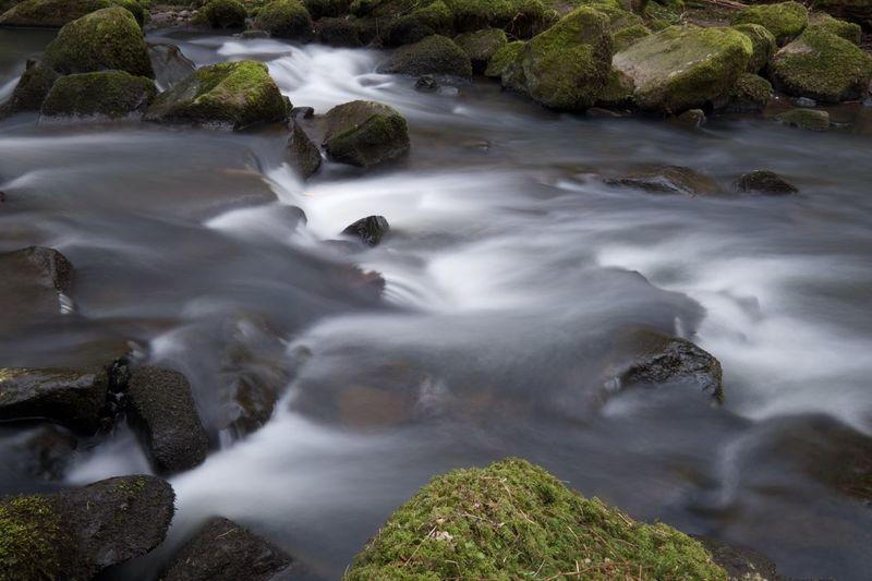 View of stream flowing through rocks