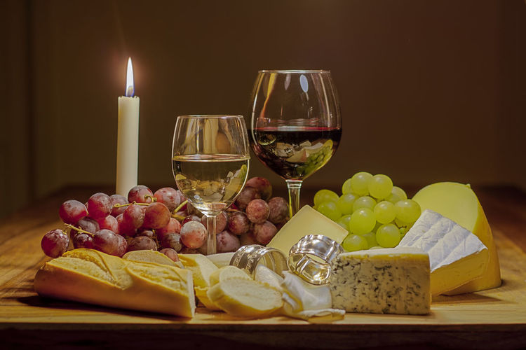 Wineglasses With Cheese And Fruits On Table By Illuminated Candle