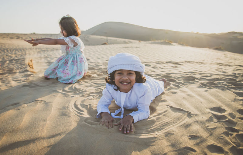 Portrait of happy boy by sister playing on sand dune