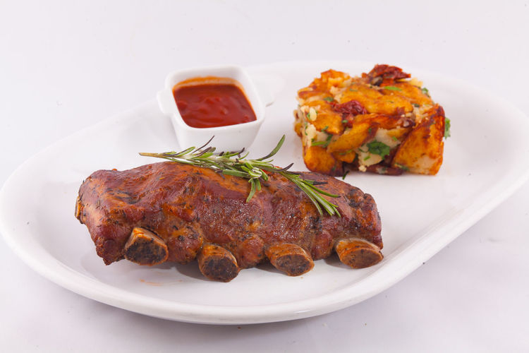 Close-up of cooked ribs in plate on table