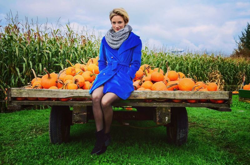Portrait of woman sitting by pumpkin on wooden cart at laity pumpkin patch