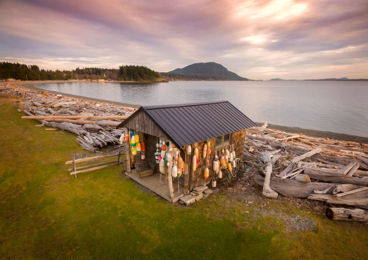 Fisherman's Shack Covered in Crab Buoys. Colorful fisherman's shack located on the west side of Lummi Island in the Puget Sound area of western Washington state. Lummi Island Pacific Northwest  Puget Sound Salish Sea Beach Beachfront Beauty In Nature Built Structure Cabin Cloud - Sky Colorful Crab Buoys Driftwood Island Mountain Nature No People Outdoors San Juan Islands Scenics Shack Sunset Tranquility Water Waterfront