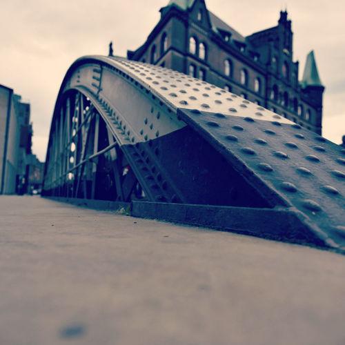 Close-up of bridge against buildings in city
