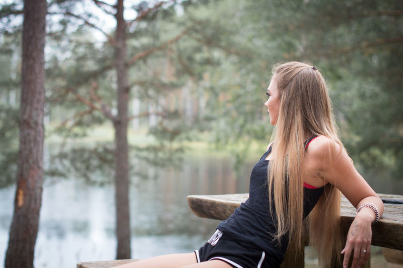 Young woman sitting on picnic table by lake