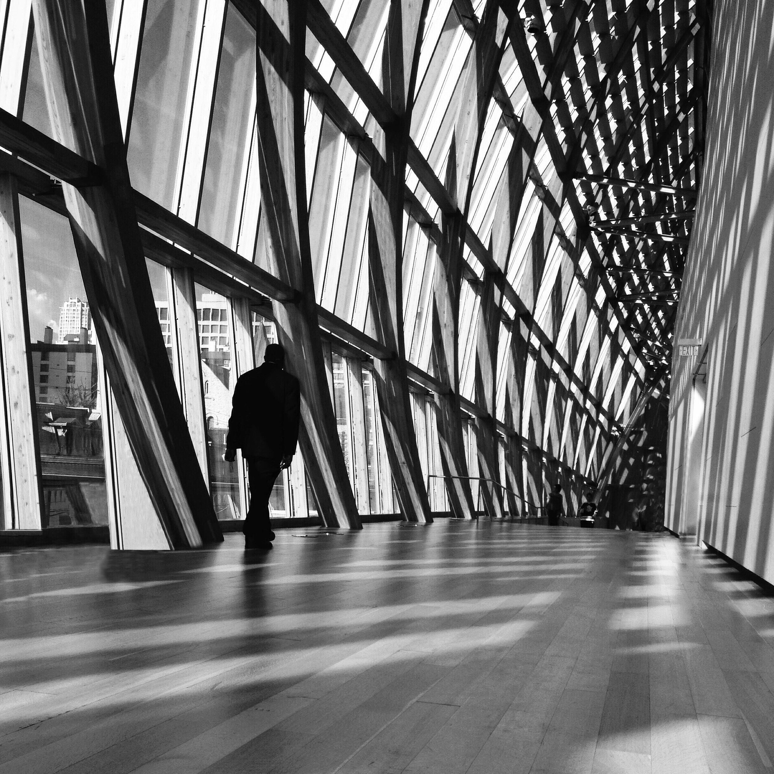 indoors, full length, lifestyles, walking, rear view, men, architecture, built structure, silhouette, person, leisure activity, standing, corridor, casual clothing, building, the way forward, window