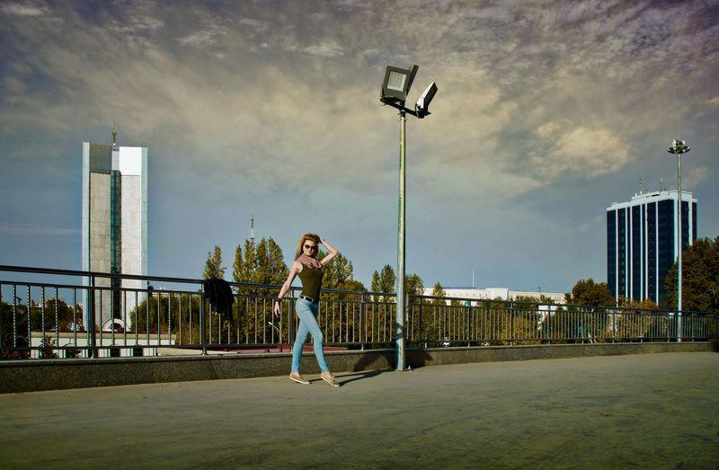 Woman posing on street against sky