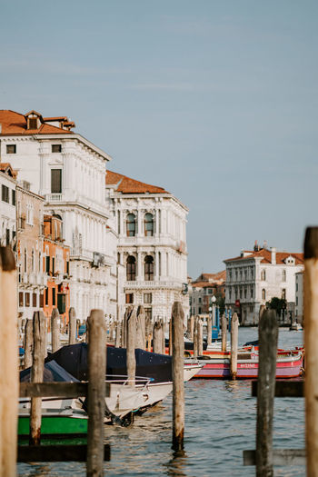 Wooden posts and boats on grand canal in city