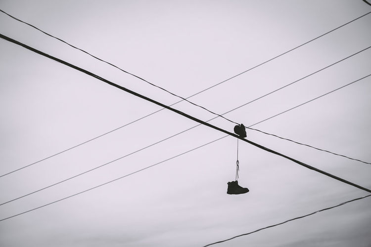 Low angle view of shoes hanging on cable against sky