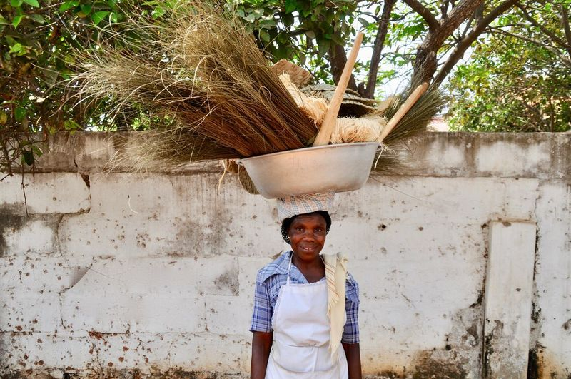 Portrait of smiling woman carrying basket on head while standing against wall
