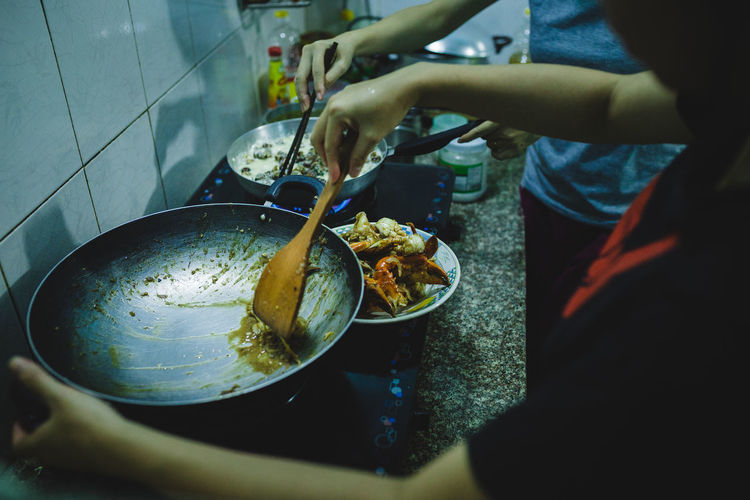 Midsection of women preparing food in kitchen