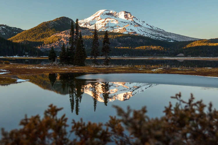 South Sister looms over Sparks Lake, where a thin sheet of October ice intrudes on the glassy reflection. Cascade Mountains Oregon Pacific Northwest  Reflection Beauty In Nature Cascades Lake Mountain Mountain Range Nature No People Outdoors Scenics Snow Snowcapped Mountain South Sister Sparks Lake Sunset Tranquil Scene Tranquility Tree Volcano Water