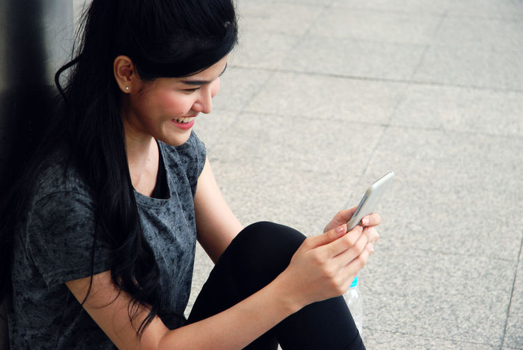 Side view of young woman using mobile phone while sitting on footpath